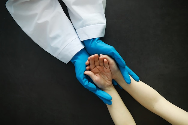 Medical concept. the doctor in gloves holds the patient's hand. the moral help of the doctor to his patients. cardiologist consultation. epidemic.