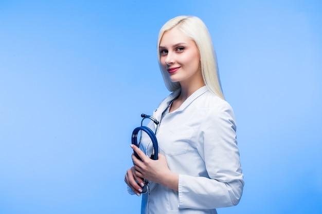 Медицинская концепция красивой женщины-врача в белом халате с фонендоскопом. студент-медик, врач общей практики. работник больницы женщина смотря камеру и усмехаясь, студия, голубой фон.