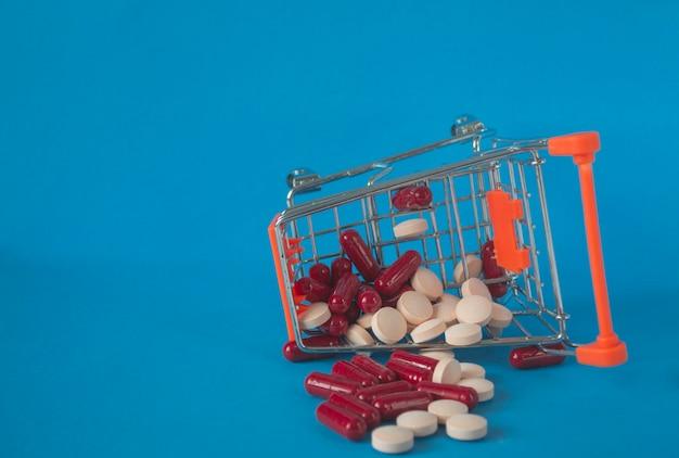 医療の概念。転倒した薬のカート、青に散らばった錠剤。コロナウイルスの薬、免疫力を高めるためのビタミン。オンライン薬局。