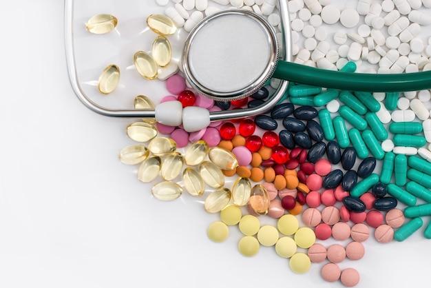医療概念の丸薬と聴診器は白い背景で隔離されます