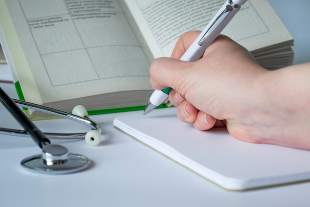 Medical concept. on the table are a stethoscope, a pen, a notebook, a book. medical background on a white background. preparation for the examination, compendium