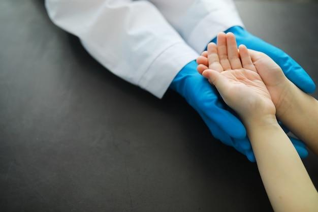 Медицинская концепция. врач в перчатках держит пациента за руку. моральная помощь врача своим пациентам. консультация кардиолога. эпидемия.