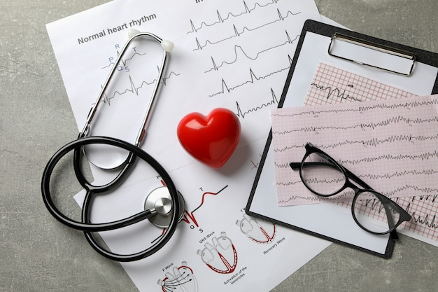 Medical concept with electrocardiogram results on gray
