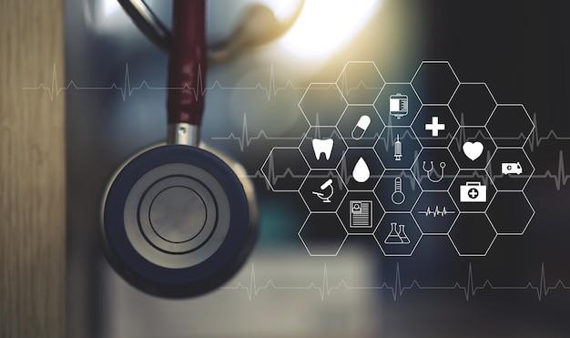 聴診器とぼやけた病院の背景に医療の白いアイコンと医療の概念