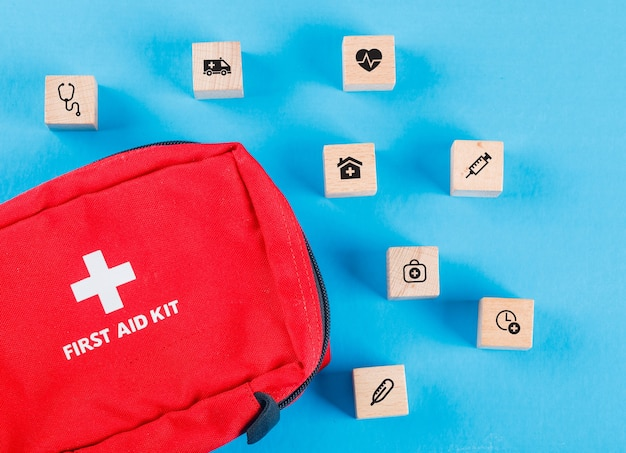 Medical concept with wooden blocks with icons, first aid bag on blue table flat lay.