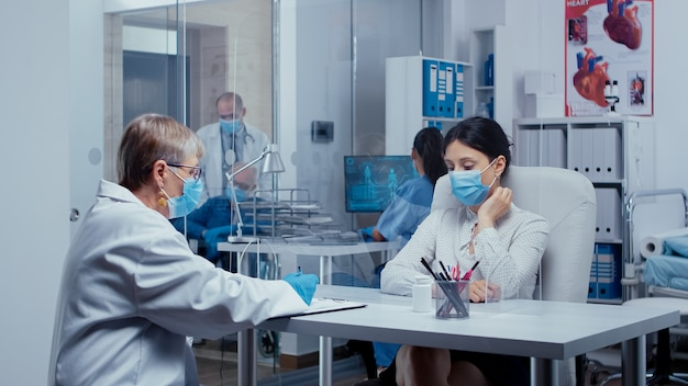 Медицинская консультация во время кризиса со здоровьем covid-19, пациент и врач в масках разговаривают через стену из оргстекла. медицинская консультация в концепции защитного снаряжения выстрел из sars-cov-2 global
