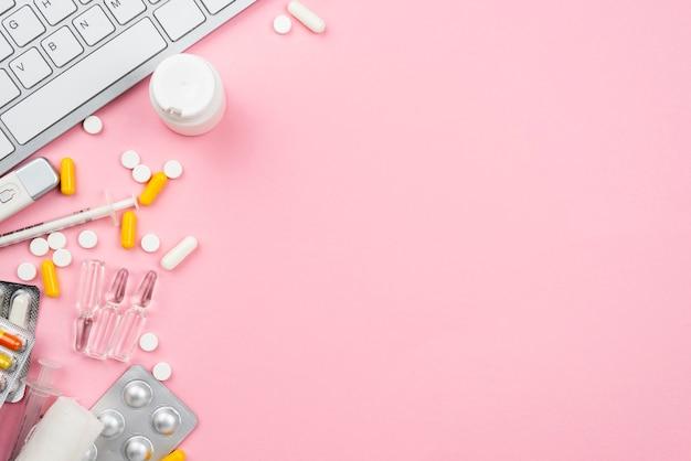Medical desk arrangement on pink background with copy space