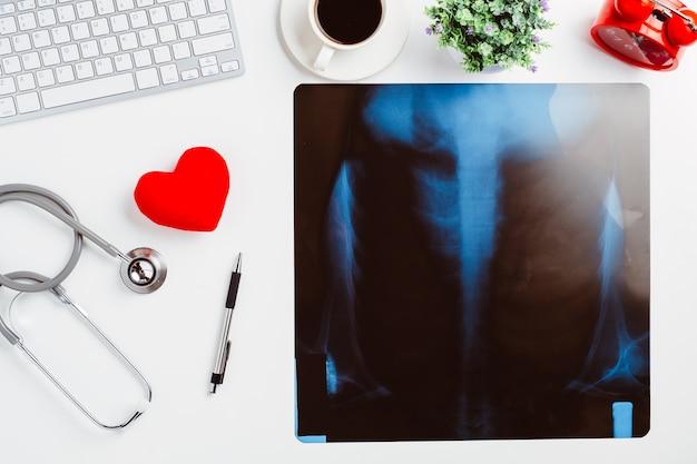 白い机の上に聴診器、心臓、ペン、ラップトップ、マウス、およびx線フィルムを備えた医療デスク。トップビュー