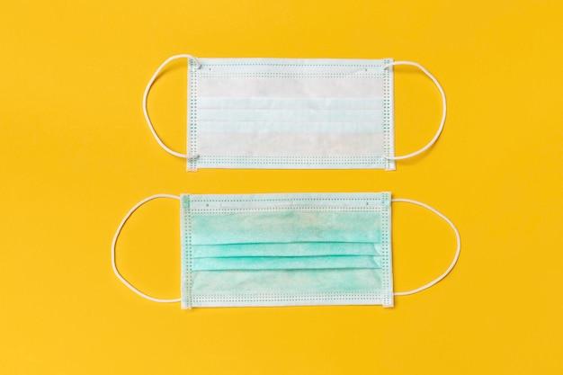 Одноразовая медицинская маска для лица на желтом фоне, защита и профилактика распространения covid-19 или нового коронавируса в ухане