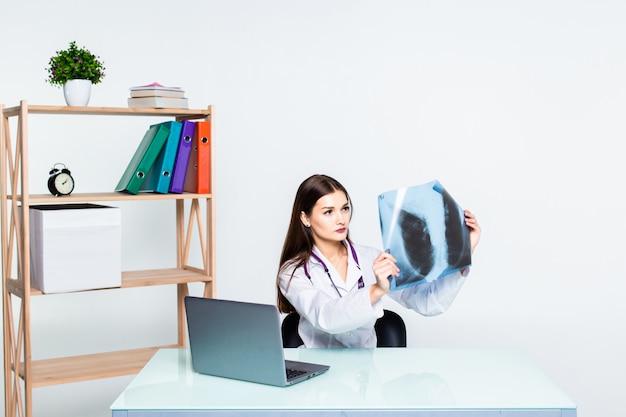 Врач анализирует рентгеновские изображения портативных, сидя на рабочий стол.