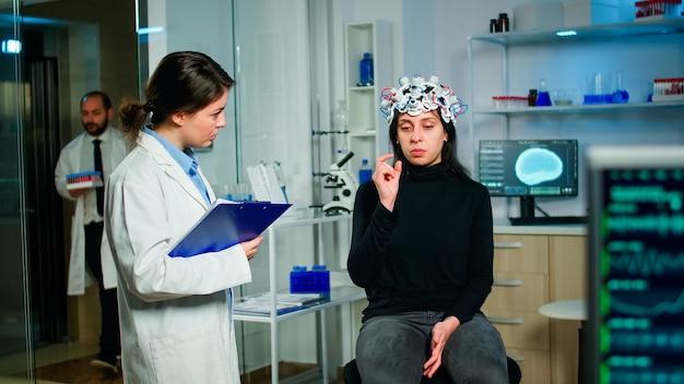Врач и пациент обсуждают симптомы заболевания во время сканирования eeg с помощью высокотехнологичной гарнитуры в лаборатории