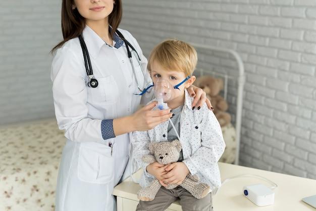 Medical doctor applying medicine inhalation treatment on a little boy