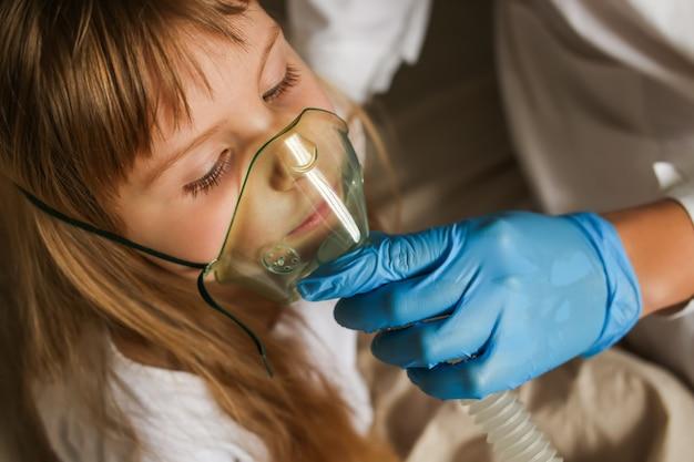 작은 여자 아기에 약 흡입 치료를 적용하는 의사