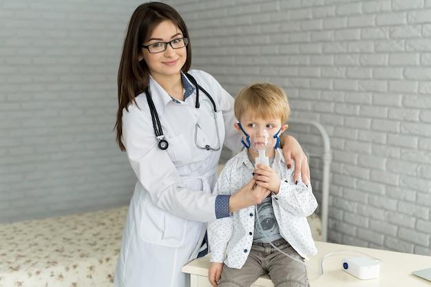 吸入器のマスクによって喘息吸入療法を受けている小さな男の子に薬の吸入治療を適用している医師。