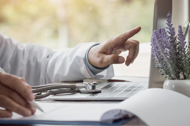 Медицинский врач кавказской медицины рассчитывает на электронном калькуляторе со стетоскопом в больнице, концепция оплаты медицинских услуг показывает результаты их успешного избирательного подхода