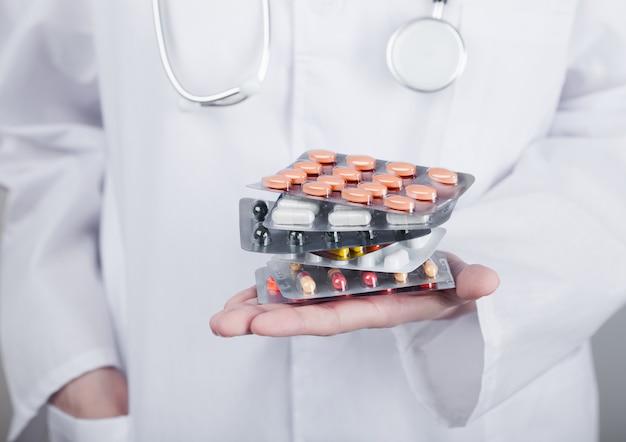 Врач держит стопку различных таблеток, антибиотиков и таблеток для лечения вирусов на серой стене больницы. макрос