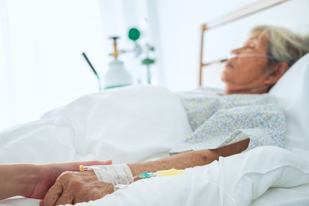 高齢者の患者の手を握って彼女を慰めている医師