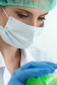 Врач в защитных перчатках и хирургической маске и шляпе, работающий с колбой с зеленой жидкостью в лаборатории. научные исследования, здравоохранение и медицинская концепция.