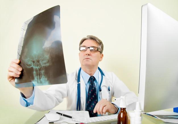Врач, глядя на рентгеновское изображение в офисе