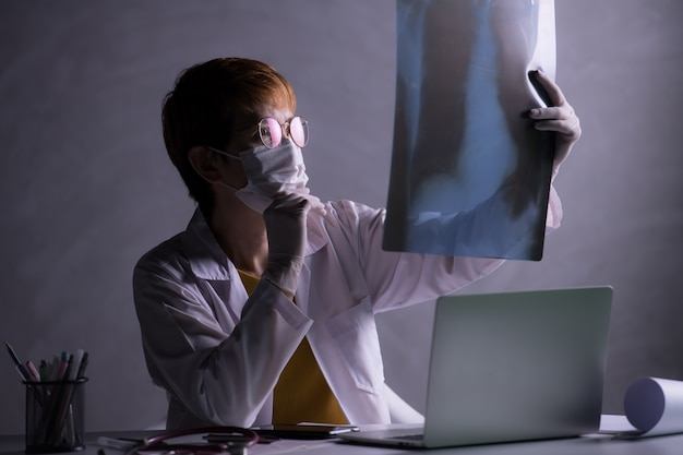 Medical doctor looking worried when inspecting x-ray film of lungs during covid-19 pandemic outbreak crisis