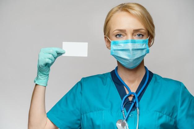 Врач медсестра женщина носить защитную маску и перчатки - показывает пустую визитную карточку
