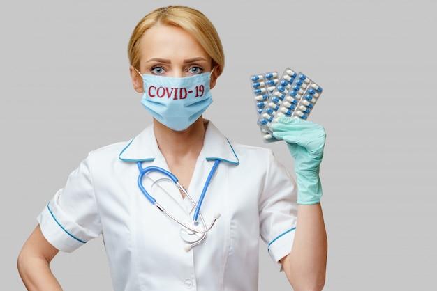 保護マスクと錠剤の水疱を保持しているラテックス手袋を着用して医師看護師女性