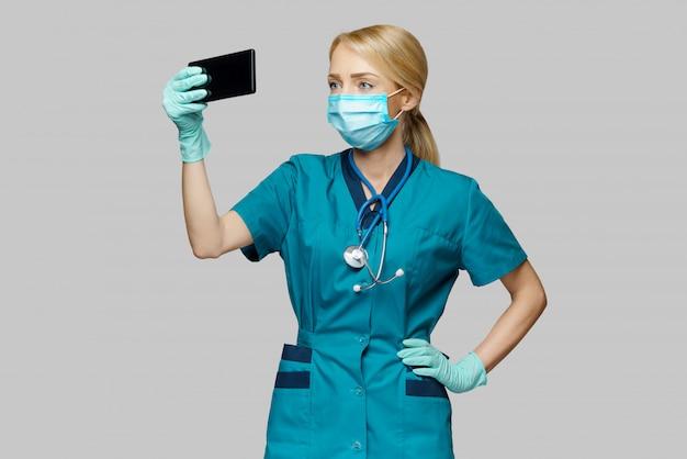 Врач медсестра женщина носить защитную маску и латексные перчатки - видео звонок по телефону