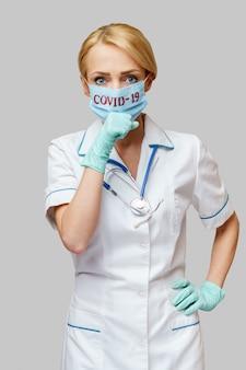防護マスクとゴムまたはラテックスの手袋を着用して医師看護師女性-咳