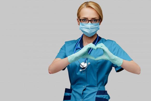 Женщина-медсестра со стетоскопом в защитной маске и латексных перчатках показывает форму сердца руками