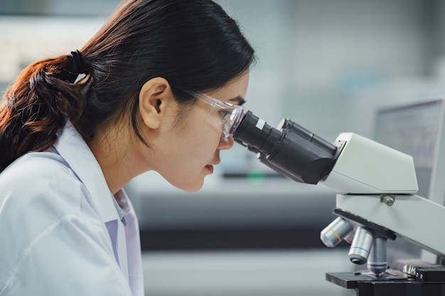 Врач или ученый, работающий в лаборатории использование микроскопа для исследования обнаруживает вирус или бактерии в образцах