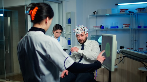 Врач, указывая на монитор компьютера с сенсорным экраном, проверяет физические реакции и нервную систему человека, носящего гарнитуру для сканирования мозговых волн в технологически продвинутой лаборатории