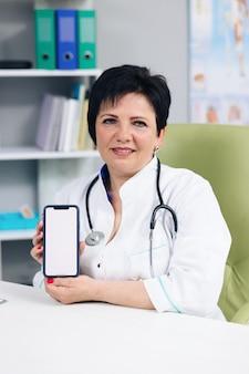 건강 클리닉에서 흰색 화면으로 스마트 폰에서 환자에게 테스트 결과를 보여주는 의사