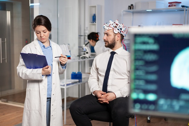 Врач говорит о симптомах болезни во время исследований с помощью высокотехнологичной гарнитуры для сканирования мозговых волн. исследователь, анализирующий состояние здоровья пациента, функции мозга, нервную систему.