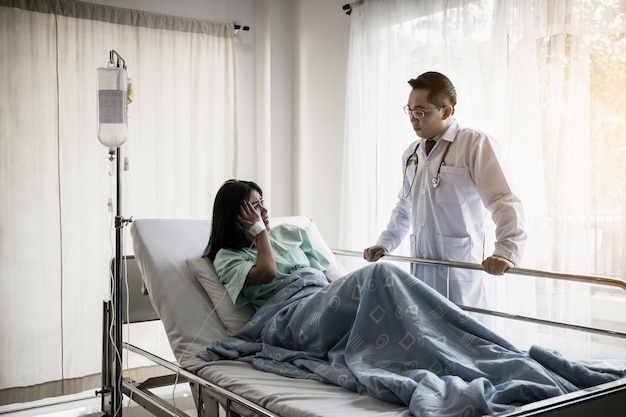 Medical doctor talking to patient and comforting her. female patient having injury lying on bed at hospital.