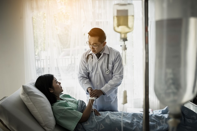 Medical doctor talking to patient and  holding her hand to comforting her