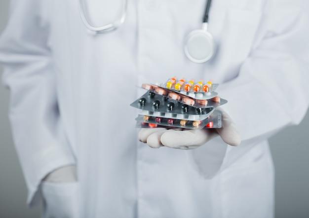 Врач в прозрачных латексных перчатках держит стопку различных таблеток на серой стене больницы. таблетки для лечения антибиотиков и вирусов.