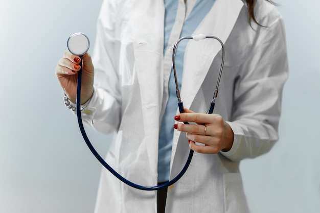 Medical doctor woman on a blue background holding stethoscope focus