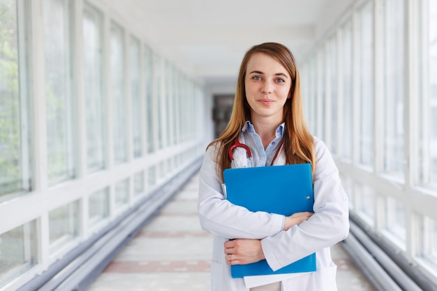 Medical doctor woman over clinic interiers background.