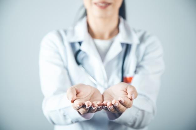 Женщина-врач показывает пустую руку