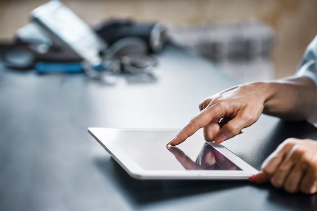 Врач женщина улыбается держать планшетный пк, используя компьютер.