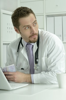 Medical doctor working with laptop and money in the office