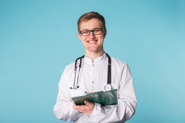 Medical doctor writing prescription over blue background with copyspace