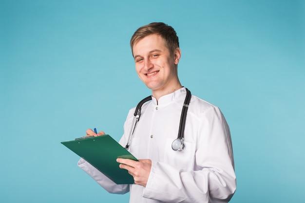 Medical doctor writing prescription over blue background.