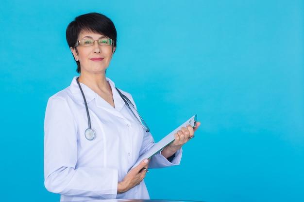 의사가 복사 공간이 있는 파란색 배경 위에 처방전을 작성합니다.