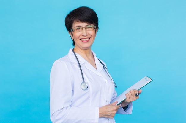 의사가 copyspace와 파란색 배경 위에 처방전을 작성