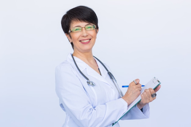 Medical doctor writing prescription over white background with copyspace