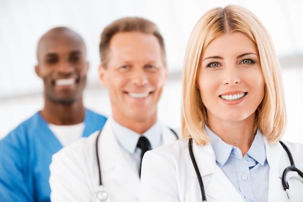 의사 팀입니다. 그녀의 동료들이 그녀 뒤에 줄지어 서 있는 동안 카메라를 보고 웃고 있는 자신감 있는 여성 의사
