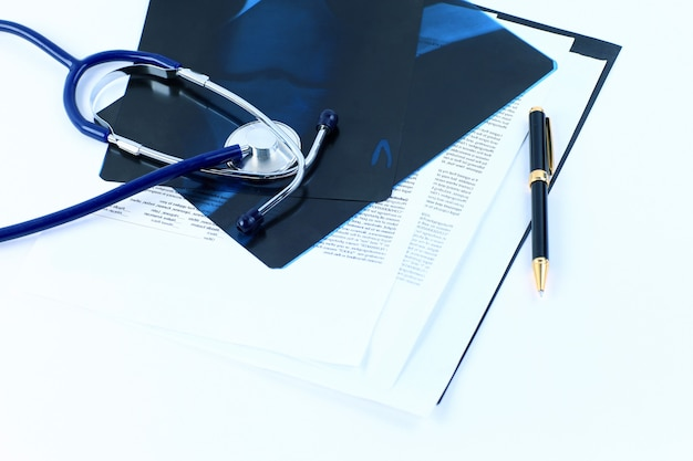 탁자 위에 펜과 청진기가 있는 형광 검사의 의료 문서
