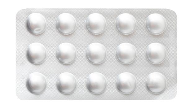 Медицинский препарат, серебряная непрозрачная пластина с таблетками, изолированные на белом фоне.