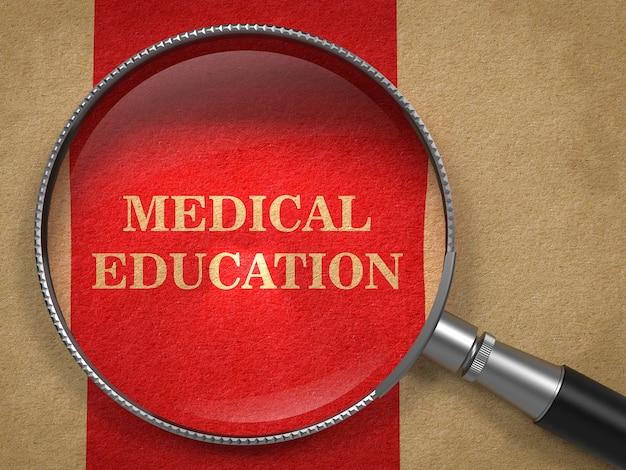 医学教育の概念。赤い縦線の背景を持つ古い紙の虫眼鏡。